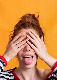 Mujer de primer plano con lengua afuera cubriendo sus ojos