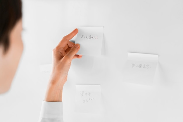 Mujer de primer plano leyendo nota adhesiva