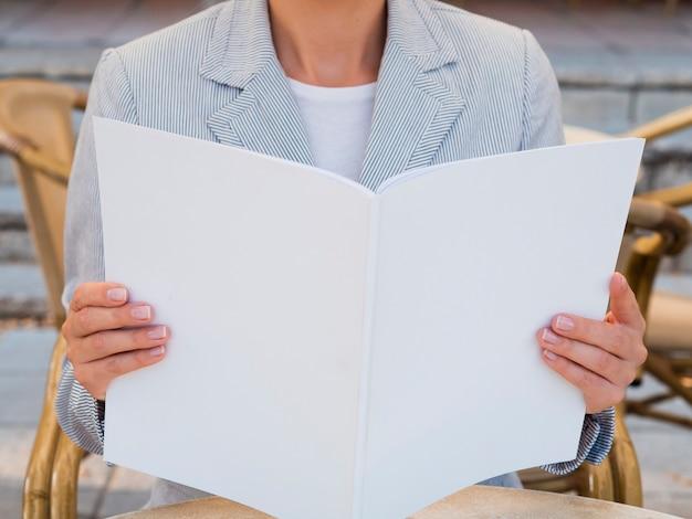 Mujer de primer plano leyendo una revista de maquetas
