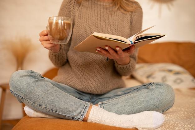 Mujer de primer plano con libro y bebida