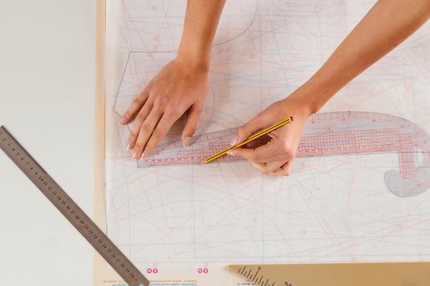 Mujer de primer plano midiendo con regla