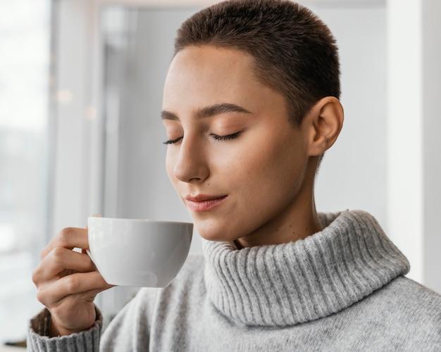 Mujer de primer plano oliendo café