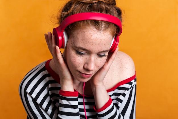 Mujer de primer plano con pecas y auriculares rojos