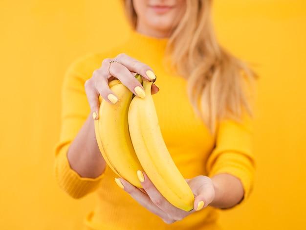 Mujer de primer plano con plátanos