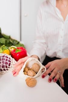 Mujer de primer plano que muestra comestibles orgánicos