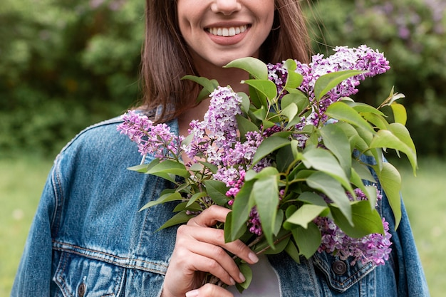 Mujer de primer plano con ramo de flores lila