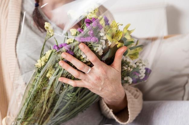 Mujer de primer plano con ramo de flores