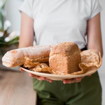 Mujer de primer plano sosteniendo la bandeja con pan