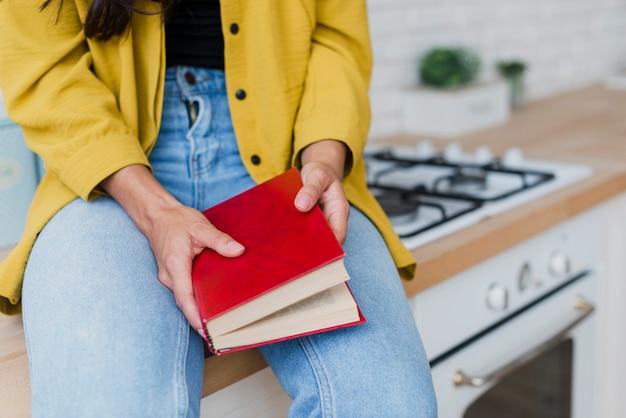 Mujer de primer plano sosteniendo libro con tapa roja
