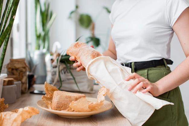 Mujer de primer plano sosteniendo pan orgánico