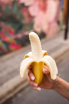 Mujer de primer plano sosteniendo un plátano