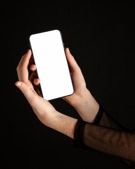 Mujer de primer plano sosteniendo un teléfono móvil