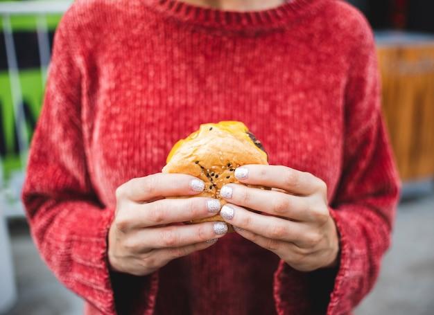 Mujer de primer plano con suéter y hamburguesa
