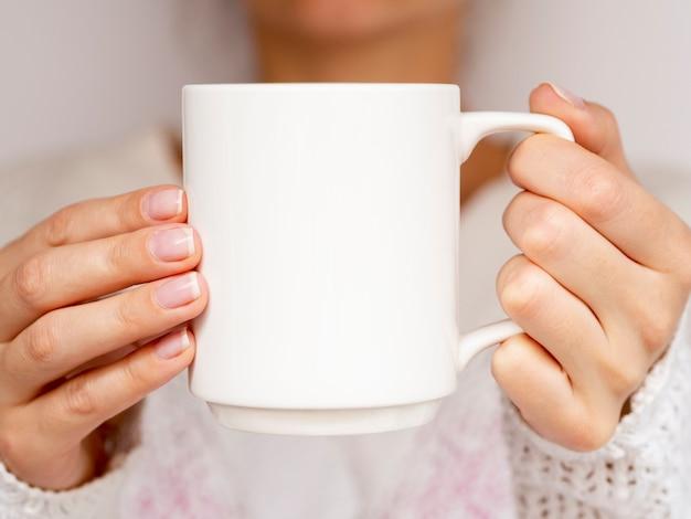 Mujer de primer plano con suéter y taza