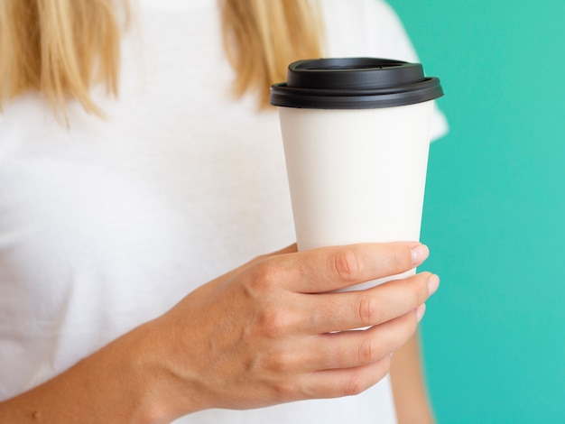 Mujer de primer plano con taza de café y fondo verde