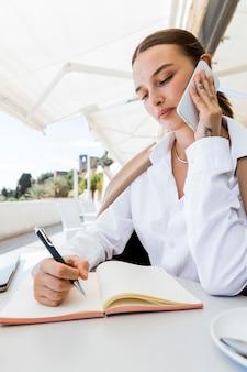 Mujer de primer plano tomando notas