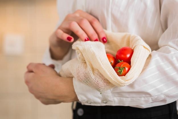 Mujer de primer plano con tomates orgánicos