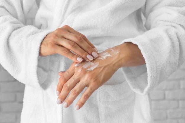 Mujer de primer plano tratando de manos crema