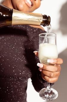 Mujer de primer plano vertiendo una copa de champán