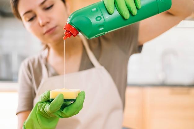 Mujer de primer plano vertiendo solución de limpieza