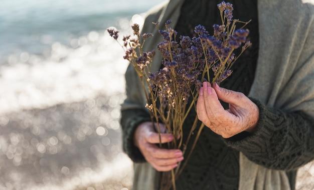 Mujer del primer que sostiene las flores púrpuras al aire libre