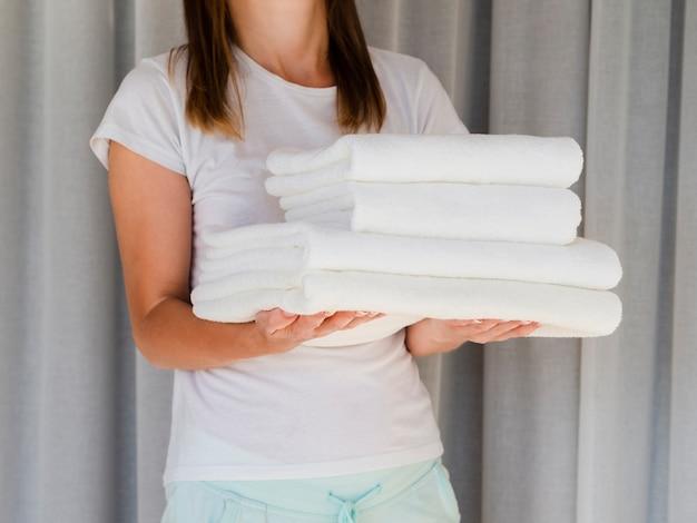 Mujer del primer que sostiene las toallas limpias dobladas blanco