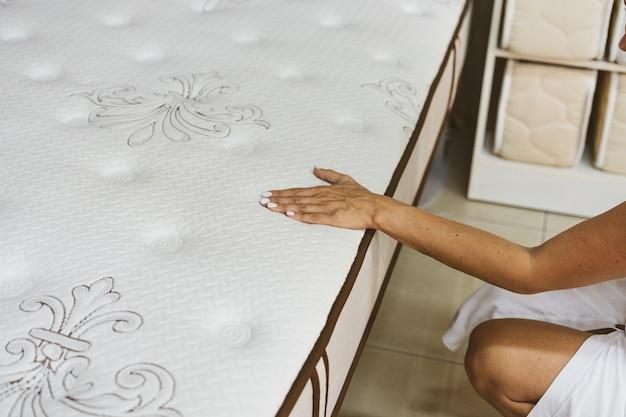 Mujer probando colchón en tienda de muebles