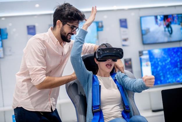 Mujer probando gafas de realidad virtual mientras está sentado en el asiento interactivo de realidad virtual. hombre de pie y mirándola.