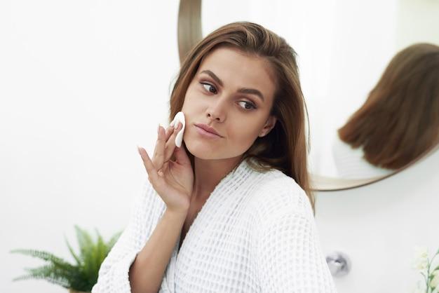 Mujer con un problema de piel de almohadilla de algodón de esponja.