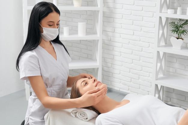 Mujer en procedimiento de masaje facial en esteticista