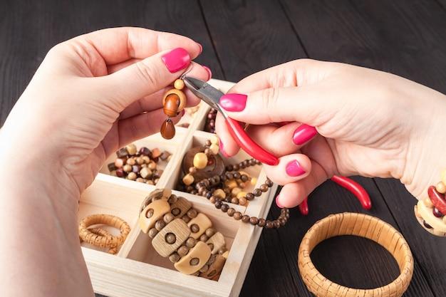 Mujer proceso hecho a mano diseño freelance trabajo en casa hacer accesorios aretes, adornos,