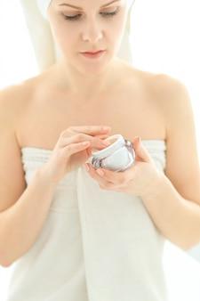 Mujer con productos cosméticos y una toalla sobre su cabeza después de la ducha