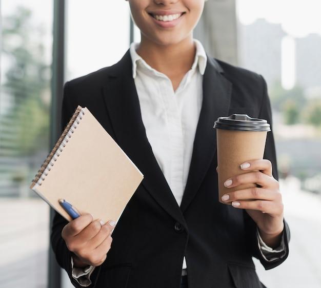 Mujer profesional con bloc de notas y café