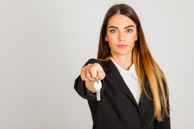 Mujer profesional entregando llaves