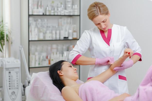 Mujer profesional haciéndole la cera a otra mujer en el brazo
