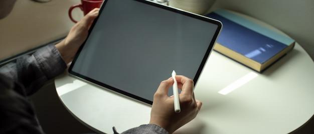 Mujer profesional independiente que trabaja con tableta digital con lápiz óptico en la mesa de café en casa