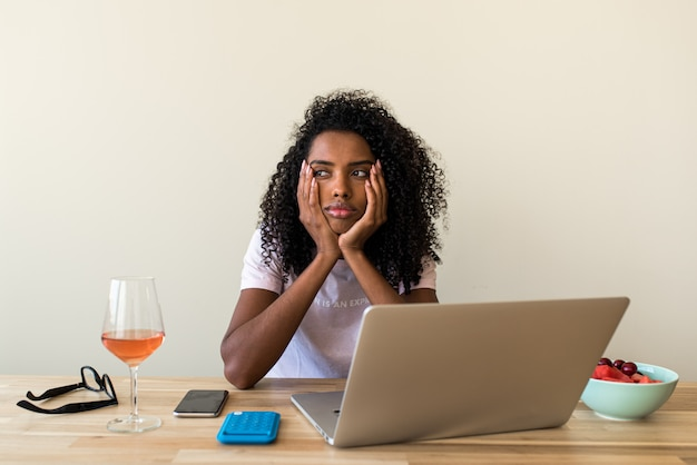 Mujer profesional independiente usando la computadora portátil en casa