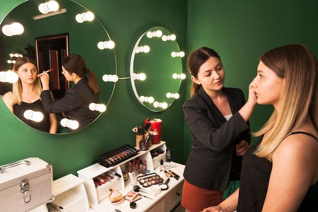 Mujer profesional maquillando chica