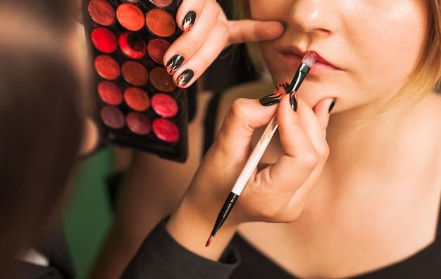 Mujer profesional maquillando los labios de una chica