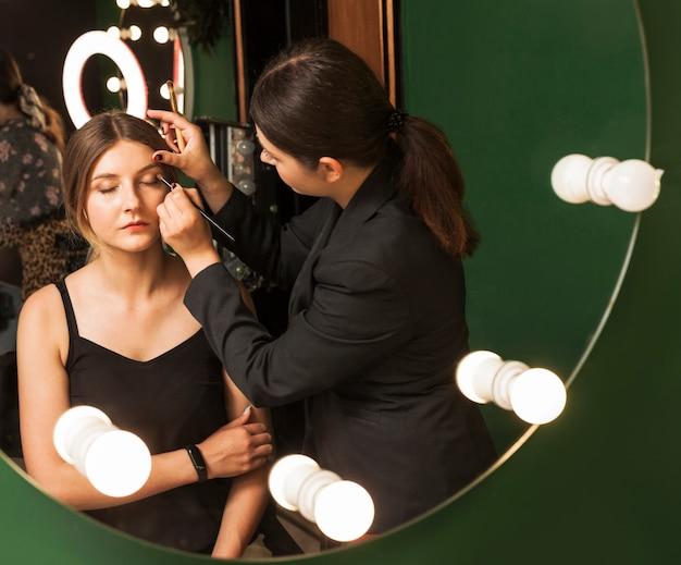 Mujer profesional maquillando ojos de una chica