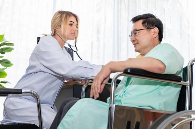 Mujer profesional médico caucásico comprobar la presión arterial con el paciente en la habitación del hospital.