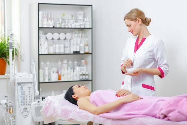 Mujer profesional mirando a una clienta tumbada