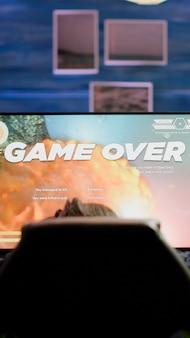 Mujer profesional molesta gamer con auriculares perdiendo el juego de disparos espaciales en la competencia de cybersport
