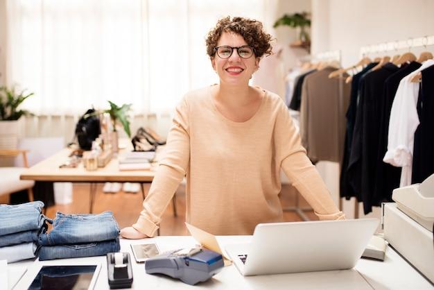Una mujer propietaria de un negocio está usando la computadora portátil