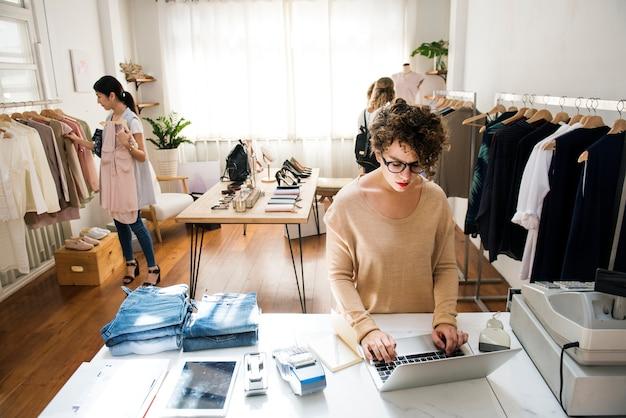 Una mujer propietaria de un negocio está usando la computadora portátil.