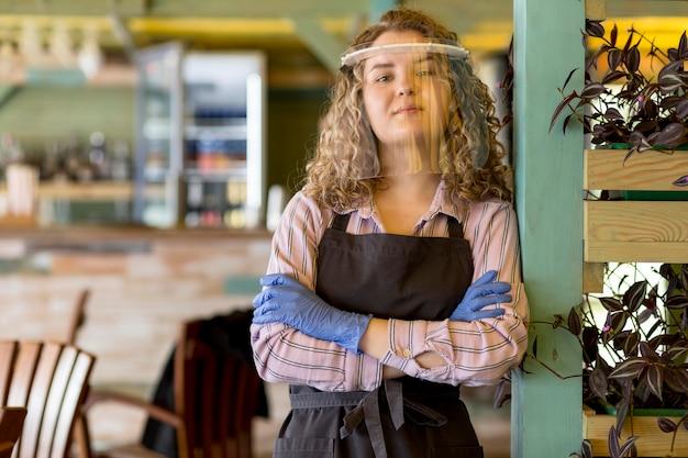Mujer con protección facial de pie con los brazos cruzados.