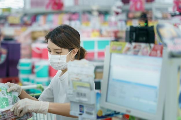 La mujer se protege de la infección de la corona con una máscara quirúrgica y guantes en el cajero escaneando el supermercado.