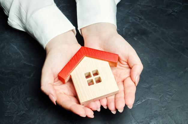 Una mujer está protegiendo una casa de madera en miniatura.