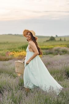 Mujer provenzal relajante en campo de lavanda. dama con sombrero de paja. chica con bolso.