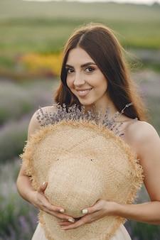 Mujer provenzal relajante en campo de lavanda. dama con sombrero de paja.